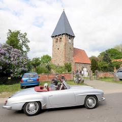 Kirche, Kapelle in Luckau / Wendland; gotischer Felssteinbau, rechteckiger Glockenturm - Mercedes Cabrio in Fahrt.