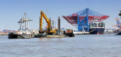 Im Parkhafen vor dem Waltershofer Hafen wird die Elbe ausgebaggert - ein Bagger auf einem Schwimmponton füllt das Baggergut in eine Schute - im Hintergrund Containerbrücken vom Terminal Burchardkai.