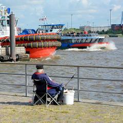 Angler an der Elbe in Hamburg Ottensen - Bug eines Schleppers; eine Hafenfähre fährt zum Anleger Oevelgönne.