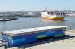 Empfangsgebäude / Abfertigungsgebäude vom Hamburger Cruise Center am Chicagokai an der Norderelbe - ein Frachter läuft in den Hamburger Hafen ein - er wird rückwärts von einem Schlepper in das Hafenbecken vom Hansahafen gezogen.