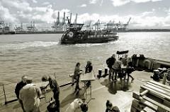 Sommer in Hamburg an der Elbe - Entspannung im Museumshafen Oevelgoenne - eine Hafenfähre fährt zum Anleger; im Hintergrund Hafenkräne / Containerkräne am Terminal Burchardkai.