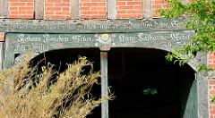 Verwittertes Holztor mit Inschrift - Wirtschaftsgebäude in Luckau / Wendland.