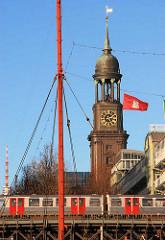 Hochbahnviadukt mit Hochbahn am Baumwall in Hamburg - Kirchturm der St. Michaeliskiche - eine Hamburg Flagge weht im Wind.