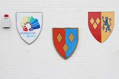 Wappen im Landkreis Lüchow-Dannenberg an der Fassade vom Rathaus in Lüchow; lks. der Samtgemeinde Lüchow, in der Mitte der Stadt Lüchow - lks. das moderne Wappen Wendland mit angedeutetem Runddorf.