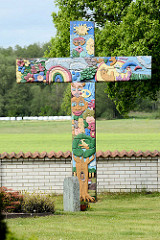 Geschnitzes farbiges Holzkreuz bei der Kirche von Luckau - angefertigt als Ferienaktion von Kindern und Jugendlichen unter der Anleitung des Künstlers Johann-Reimer Schulz.