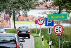 Ortschild Wulksfelde - Strassenverkehr; im Hintergrund eine Scheune vom Gutshof.