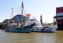 Fischkutter HBK 92 und das SAR Schiff Fritz Behrens am Anleger in Hamburg Finkenwerder; der Seenotrettungskreuzer wurde 1981 gebaut und hat zwei Dieselmotoren mit 2076 PS.