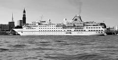 Das Kreuzfahrtschiff HANSEATIC läuft zu einer Expiditionskreuzfahrt aus dem Hamburger Hafen aus; das Passagierschiff hat eine Länge von 122,80 m und eine zugelassene Passagierzahl von 184; im Hintergrund der Kirchturm der St. Michaeliskirche / Michel