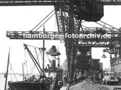 Kohlekai am Altonaer Hafen; der Greifer der weit ausladenden Krananlage holt die Kohle aus dem Laderaum des Frachters  und lädt seine Fracht am Kai ab. Dort lieg die Kohle in Bergen  - ein Lastwagen mit grossem Anhänger wartet. (ca. 1930)