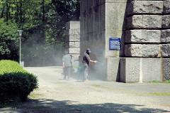 Der Sockel vom Hamburger Bismarckdenkmal ist mit Grafitti beschmiert; Arbeiter säubern den Stein mit Druckluft.