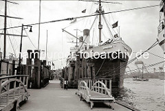 Das Passagierschiff MONTE OLIVIA der Hamburg Südamerikanischen Dampfschifffahrt - Gesellschaft liegt bei der Überseebrücke am Ponton; über die Gangway verlassen Passagiere den 1925 gebauten Dampfer. Im Hintergrund die Helgen der Deutschen Werft