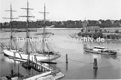 Blick von Finkenwerder Richtung Elbe ca. 1939; ein Segelschiff liegt am Steg - es ist mit Tauen an den Duckdalben fest gemacht. Eine Hafenfähre hat von den Finkenwerder Landungsbrücken abgelegt und fährt Richtung Elbe. Dahinter ist das Hamburger L