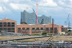 Bilder aus dem Hamburger Hafen - Lagerhallen in Hamburg Steinwerder - dahinter das Gebäude der Elbphilharmonie in der Hafencity.