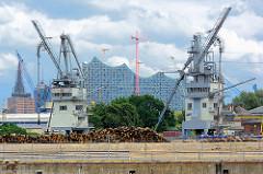 Blick über den Kaiser Wilhelm Hafen zu einem Getreideheber im Kuhwerder Hafen - im Hintergrund die Fassade der Elbphilharmoni in der Hamburger Hafencity.