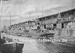 Hafenkai in Hamburg Altona - ein kleiner Frachter liegt an der Kaimauer, seine Ladung wird auf Schuten gelöscht; der Lastkahn re. hat seinen Laderaum mit Holz abgedeckt, damit seine Fracht nicht nass werden kann. (ca. 1935)