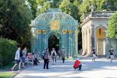 Gitterpavillon mit Sonnensymbol am Schloss Sanssouci / Potsdam - Touristen fotografieren sich in der histoirschen Anlage.