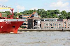 Das Container-Feederschiff RUMBA läuft in den Hamburger Hafen ein - am Elbufer der Altonaer Kaispeicher, erbaut 1924; Architektur in Neumühlen, Stadtteil Hamburg Ottensen.