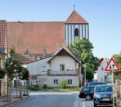 Wohnhaus und Kirche von Wusterhausen. Die Pfarrkirche St. Peter und Paul ist ursprünglich eine spätromanische Basilika von etwa 1229. In mehreren Bauabschnitten wurde sie bis 1479 zur dreischiffigen gotischen gewölbten Hallenkirche erweitert.
