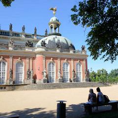 Seitengebäude des Neuen Palais in Potsdam, Park Sanssouci - Parkbank im Schatten unter Bäumen.
