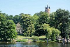 Blick über die Havel zum Ufer am Park Babelsberg; badende Menschen - Matrosenhaus und Aussichtskuppel vom Flatowturm. Seit 1990 gehört der Park Babelsberg als Teil der Schlösser und Parks von Potsdam und Berlin zu Liste des UNESCO Welterbe.