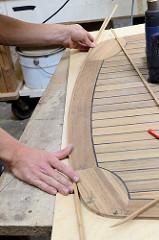 Die Heckkante des Mahagonie-Decks werden in der Werkstatt mit Massivholzleisten versehen.