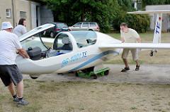 Der Segelflieger wird vorsichtig auf einen Rollwagen gesetzt und in die Halle geschoben.