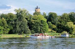 Sportboote ankern im Paket vor dem Park Babelsberg in der Sonne - Aussichtskuppel vom Flatower Turm. Seit 1990 gehört der Park Babelsberg als Teil der Schlösser und Parks von Potsdam und Berlin zu Liste des UNESCO Welterbe.
