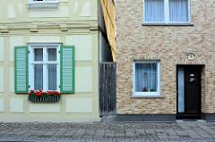 Alt + neu; Wohnhäuser in der Kyritzer Strasse von Wusterhausen, Dosse - Fachwerkhaus, restauriert mit Fensterluken und Blumenkasten - Hausfassade mit Ziegelverkleidung.