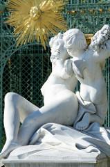 Skulptur Flora mit Zephir am Gitterpavillon beim Schloss Sanssouci - goldenes Sonnensymbol.
