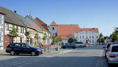 Historische Wohnhäuser - Geschäftshäuser am Markt von Wusterhausen, Dosse; hinter dem Rathaus die St. Peter und Paul Kirche.
