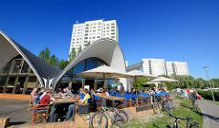 Betonschalenbau am Ufer der Neustädter Havelbucht in Potsdam. Das 1983 errichtete Architekturdenkmal der Ost-Moderne wurde vom Bauingenieur Ulrich Müther als Café Seeroose entworfen. Gäste sitzen in der Sonne am Wasser.