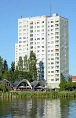 Betonschalenbau am Ufer der Neustädter Havelbucht in Potsdam. Das 1983 errichtete Architekturdenkmal der Ost-Moderne wurde vom Bauingenieur Ulrich Müther als Café Seeroose entworfen. Gäste sitzen in der Sonne am Wasser; dahinter ein Hochhaus, Platten
