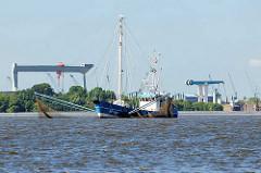 Finkenwerder Fischkutter mit Netzen auf der Elbe vor Hamburg Neuenfelde - im Hintergrund re. die Klappbrücke über die Este - lks. der Werftkran der Sietas-Werft.