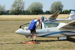 Piloten der Segelflugzeuge auf dem Verkehrslandeplatz Kyritz legen ihre Fallschirme an.