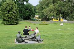 Liegewiese auf der Freundschaftsinsel in Potsdam - Menschen und Bronzeskulptur - Schönheit der Menschen in der Natur, Margret Midell, 1974; im Hintergrund fährt auf der Havel, Neue Fahrt ein Ausflugsschiff.