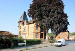 Backsteinvilla - Wohnhaus mit gelber Ziegelfassade - grosse Blutbuche / Rotbuche; im Hintergrund das Bahnhofsgebäude.
