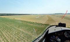 Landeanflug auf dem Verkehrslandeplatz Kyritz mit dem Segelflugzeug - die Landebahn ist entsprechend markiert. An der Cockpithaube ist ein roter Wollfaden / Haubenfaden angebracht; dieser Faden zeigt dem Piloten die Richtung der Luftströmung am Flugz