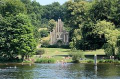 Sommer in Potsdam - Menschen baden in der Havel / Tiefer See am Ufer vom Park Babelsberg - Matrosenhaus im Stil der deutschen Gotik, Architekt Johann Heinrich Strack, erbaut 1842. Seit 1990 gehört der Park Babelsberg zum UNESCO Welterbe.