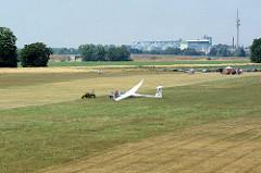 Landeanflug mit dem Segelflugplatz Kyritz; ein Segelflugzeug wird mit dem Flugzeugschlepper nach der Landung wieder zur Startposition gebracht.
