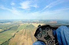 Cockpit mit Instrumenten eines Segelflugzeugs beim Flug - unten sind Felder und Wiesen sowie im Hintergrund die Hansestadt Kyritz zu erkennen.