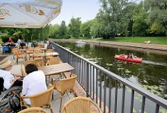 Sommer in Potsdam - Café am Havellauf Alte Fahrt - Tretboot auf dem Wasser; ein Sportboot hat vom Kai abgelegt.