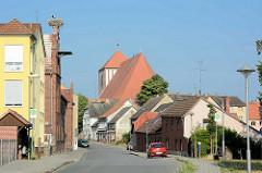 Blick durch die Borchertstrasse in Wusterhausen / Dosse zur Pfarrkirche St. Peter und Paul - lks. ein alter Fabrikschornstein mit Storchennest.