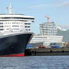 Bug der Queen Mary 2 am Kreuzfahrtterminal Hafencity im Hamburger Hafen - im Hintergrund die moderne Architektur vom Maro Polo Tower und der Hamburger Elbphilharmonie.