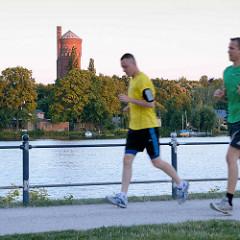 Abend an der Havel in Potsdam - Abendsonne fällt auf den Wasserturm auf der Halbinsel Hermannswerder, Jogger im Lauf.