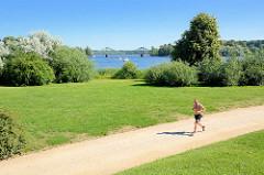 Babelsberger Park - Jogger auf dem Weg am Havelufer; im Hintergrund die Glienicker Brücke.