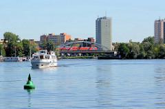 Blick über den Templiner See, Potsdamer Havel - grüne Fahrwassertonne, ein Sportboot fährt flussabwärts - ein Zug überquert die Eisenbahnbrücke.