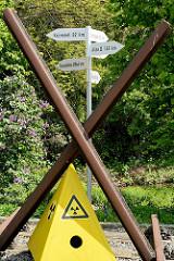 Das X aus Bahnschienen; Symbol der Anti Atom Bewegung im Wendland; Holzschilder mit Entfernungsangaben: Krümmel, Fukushima, Asse und Gorleben.