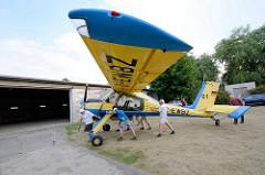 Vereinsmitglieder vom Flugsport-Club Kyritz schieben das Schleppflugzeug PZL-104 Wilga zur Halle.