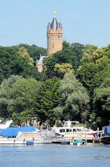 Marina mit Sportbooten, Tiefer See / Havel in Potdam - Park Babelsberg mit Flatowturm zwischen Bäumen. Seit 1990 gehört der Park Babelsberg als Teil der Schlösser und Parks von Potsdam und Berlin zu Liste des UNESCO Welterbe.