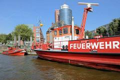 Löschboote der Hamburger Feuerwehr am Anleger Kehrwieder, Hafencity Hamburg - im Hintergrund Bürogebäude am Sandtorkai.